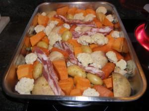 On répartit les légumes en une couche dans un grand plat à four et on insère les tranches de poitrine de porc, verticalement et couenne vers le bas.