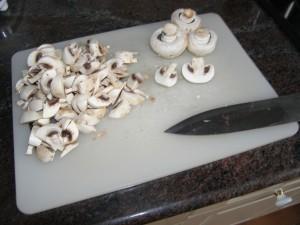 Les champignons de Paris en cours d'éminçage en fines lamelles.